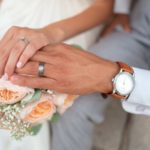 couple-holding-hands-showcasing-wedding-rings-flowers-in-the-background